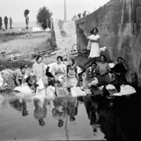 Grupo de mujeres lavando en el río.